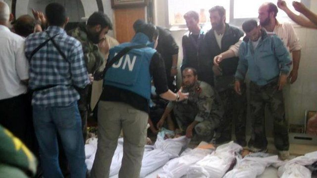 UN observers at a hospital morgue before their burial in the central Syrian town of Houla