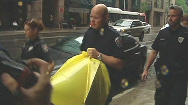 Police carry a yellow bag