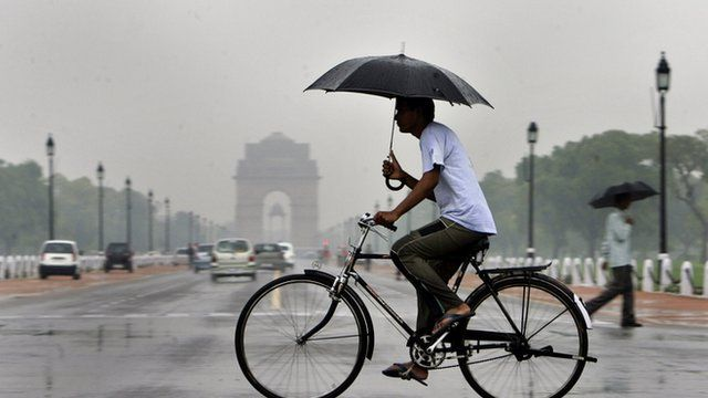 An Indian cyclist carries an umbrella during a rain shower in New Delhi