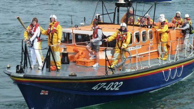 Olympic torch on a lifeboat