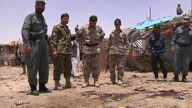 Soldiers stand over blood-stained ground
