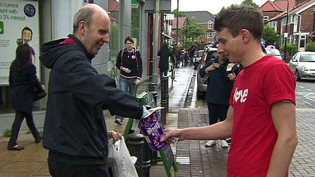 A volunteer gives a passer-by a chocolate