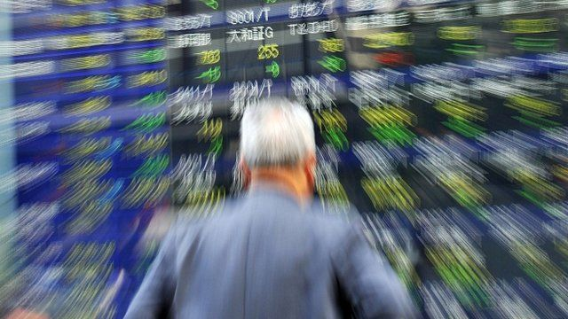 A businessman gazes at a share prices board in Tokyo