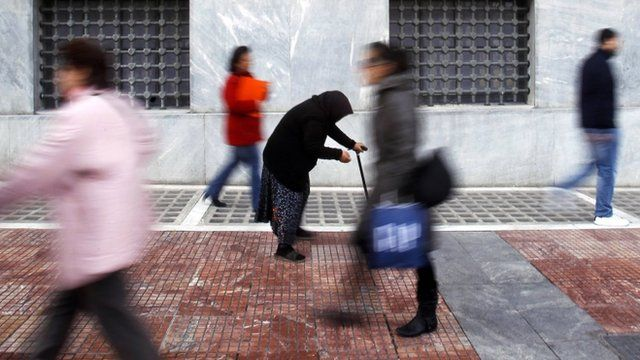 A woman begs as shoppers walk by in central Athens