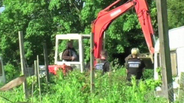 Dave Dawson in his digger with two police officers watching