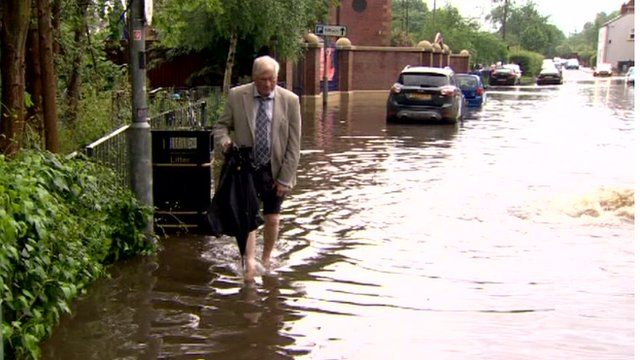 A man walks through flood water