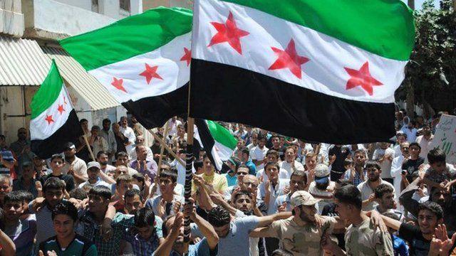 Demonstrators waving Syrian flags