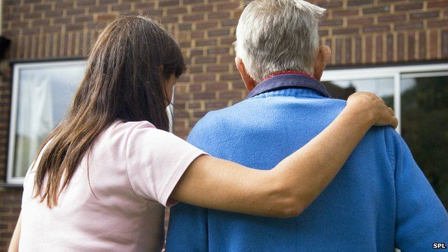 Woman carer with her arm around an elderly man