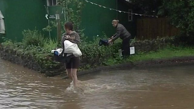 Woman carries baby across flood water