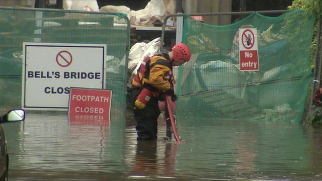 Worker tries to clear a flooded street