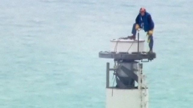 An engineer unscrews a TV antenna on top of the Willis Tower.