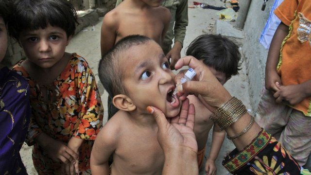 A Pakistani health worker gives a polio vaccine to a child in Lahore, Pakistan