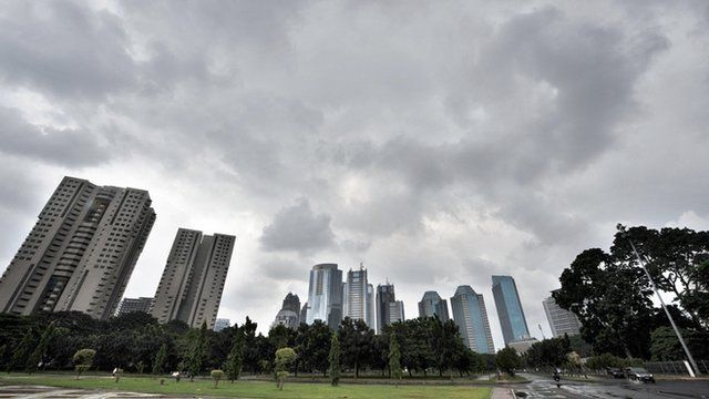 Dark clouds hang over the skyline of downtown Jakarta