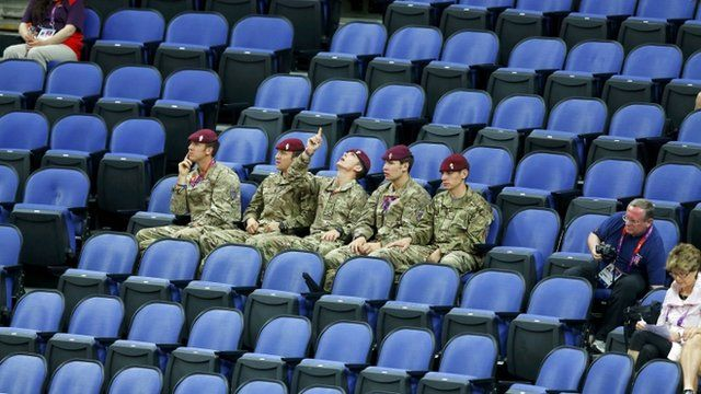 Soldiers sit amid empty seats