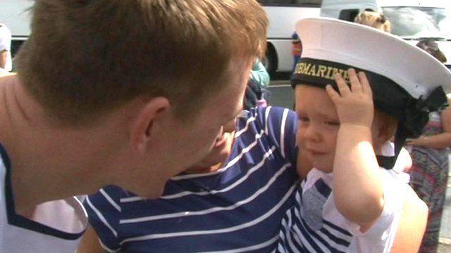 Sailor smiling at his baby son