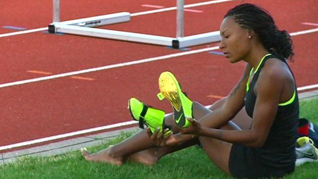 Female athlete relaxing on grass by track