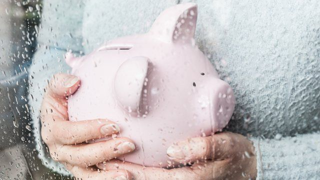 woman holding a piggy bank at her rainy window