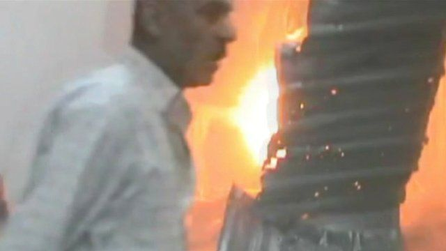 Buildings on fire as man walks past in southern Damascus