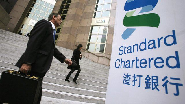 People walk outside the main branch of the Standard Chartered Bank in Hong Kong