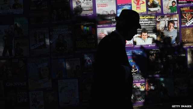 Man walks past a board promoting shows at the Edinburgh Fringe