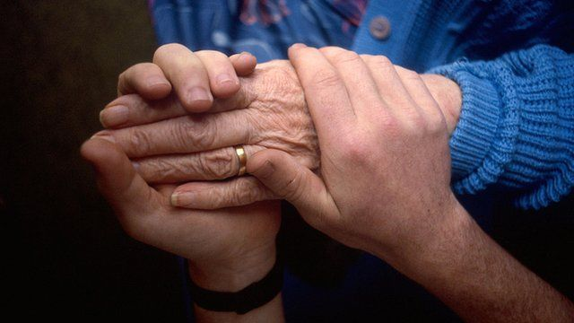 An elderly person holds the hands of a carer
