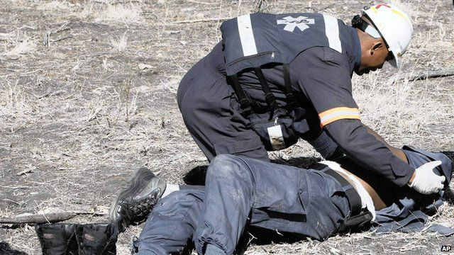 An injured policeman is tended after he was attacked and injured by striking Lonmin miners near Rustenburg.