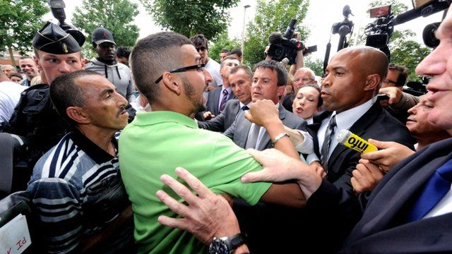 French Interior Minister Manuel Valls (centre) is heckled