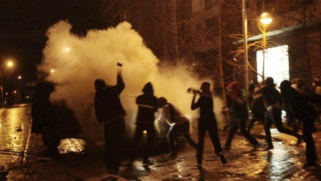 Students clash with a riot police vehicle