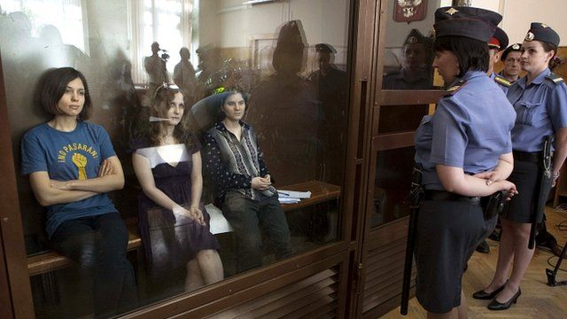 The three band members sit behind a glass partition in court