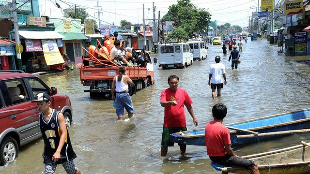 Residents commute along a flooded stretch of road north of Manila on 11 August