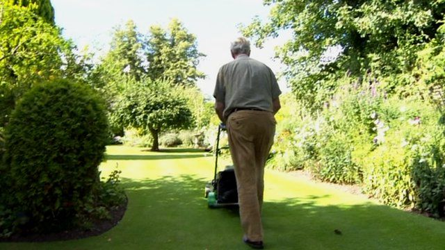 Dr Chisholm Ogg mowing his lawn