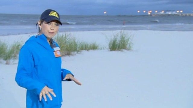 Meteorologist Ginger Zee on the beach in front of growing surf in Gulfport, Mississippi