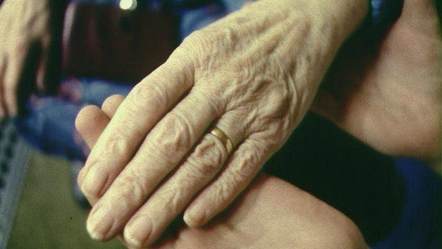 Elderly person holding hands with a carer