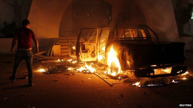 A protester stands next to a burning car in Libya