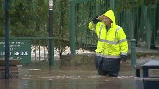 Man walks through flood water in Morpeth