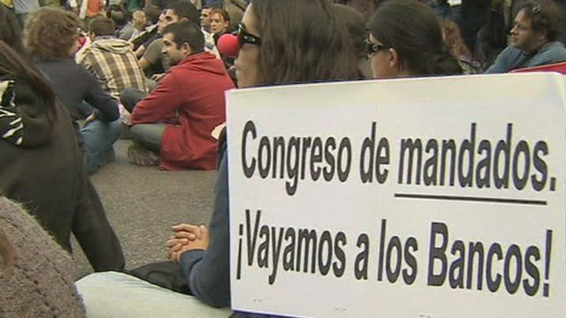 Young protesters with placards staging a sit-in protest in central Madrid