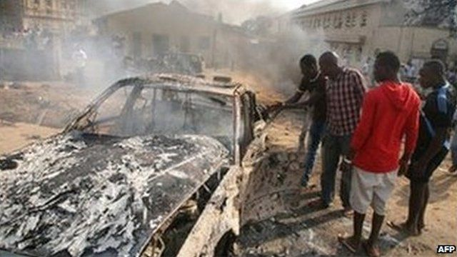 Men look at the wreckage of a car following a bomb blast at St Theresa Catholic Church outside the Nigerian capital Abuja on December 25, 2011