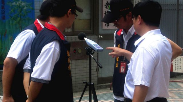 Inspectors from Taipei's Department of Environmental Protection read a sound level meter in Taipei, Taiwan, 16 July 2012