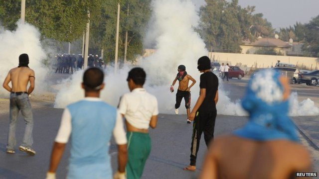 Protesters take cover from tear gas fired by riot police during clashes in the Bahraini capital of Manama.