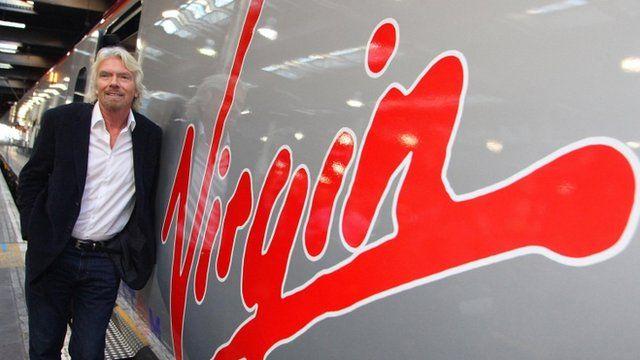 Sir Richard Branson standing next to a Virgin train