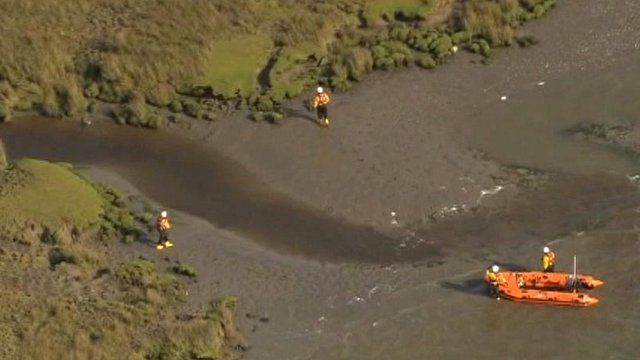 Rescue workers search the estuary