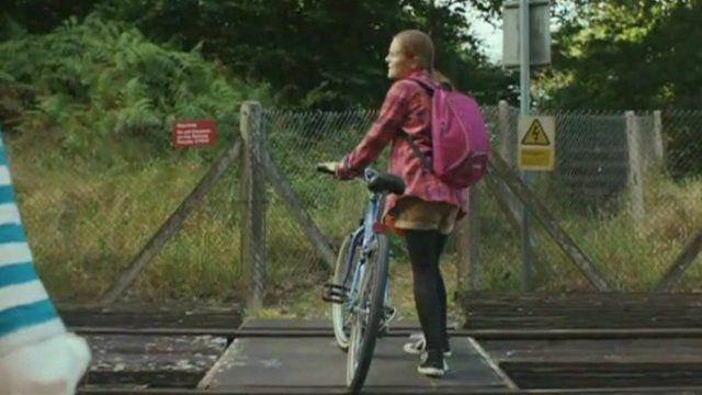 Girl with bike standing on rural railway crossing