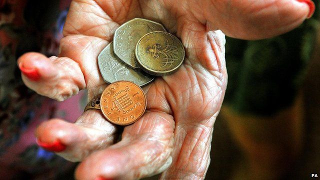 Pensioner's hand holding coins