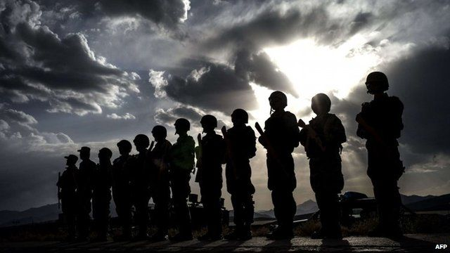 Afghan policemen stand guard for a debriefing during an exercise