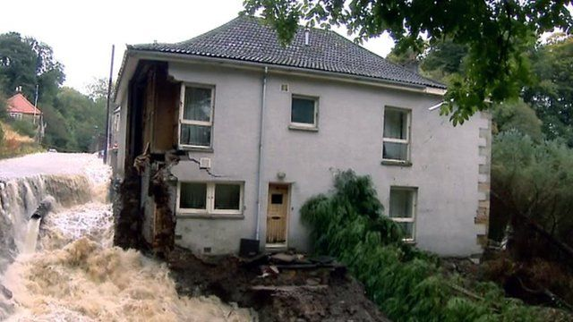 House with a wall missing surrounded by flood water