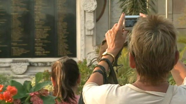 Woman takes picture of memorial wall