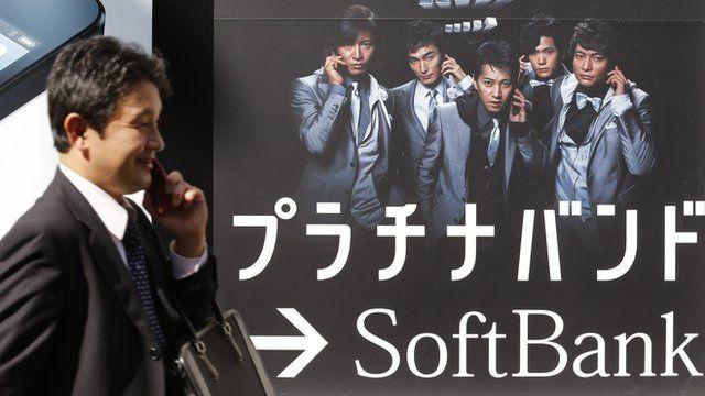 A man walks past a Softbank advertisement board in Tokyo