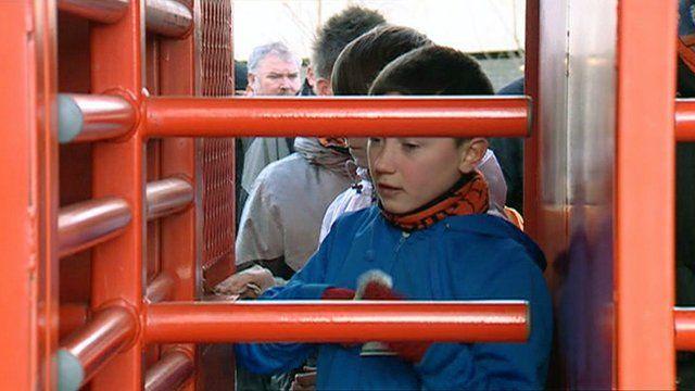 Football fans going through a turnstile