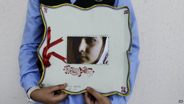 Pakistani student holds a picture of Malala Yousafzai during a tribute at the Pakistani Embassy in Abu Dhabi, Oct 15 2012.