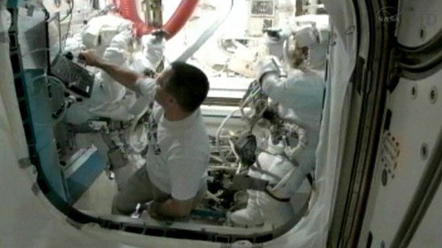 Station commander Sunita Williams and flight engineer Akihiko Hoshide dancing in their spacesuits, with Kevin Ford at the airlock